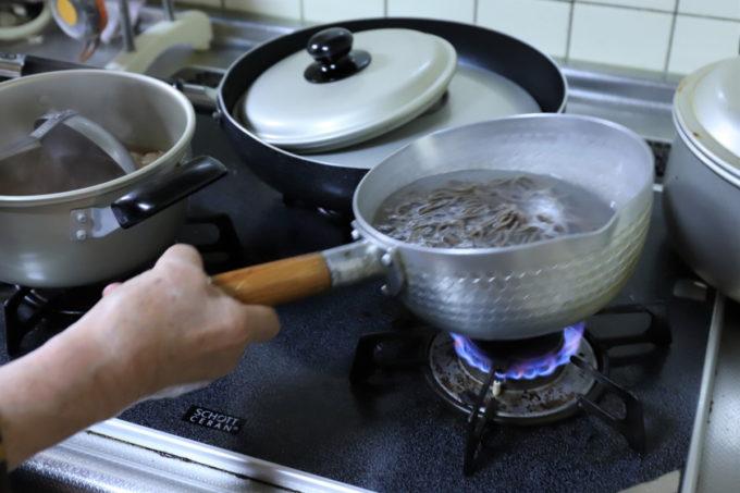 茹で上がった蕎麦の鍋を持っている祖母(おばあ)