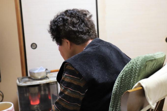 灯油ストーブの前に座る祖母(おばあ)