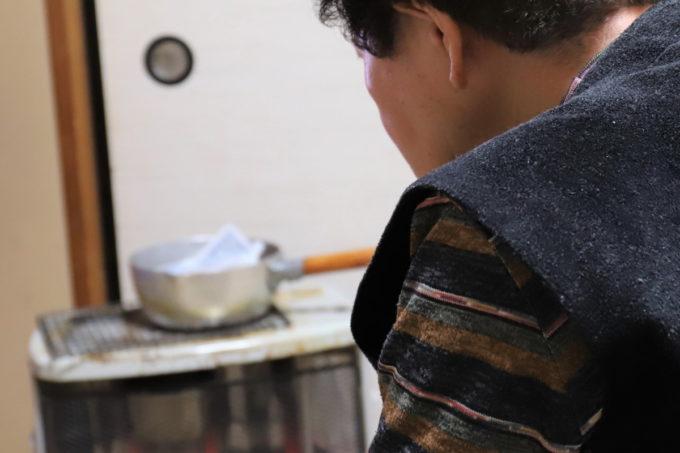灯油ストーブの上の片手鍋と、その前に座る祖母(おばあ)