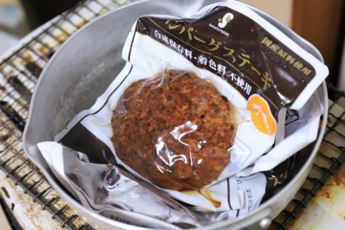 鍋で湯せんしているパックのハンバーグステーキ