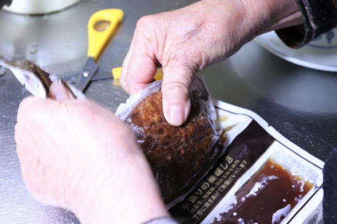 真空パックからハンバーグを取り出す祖母(おばあ)の手