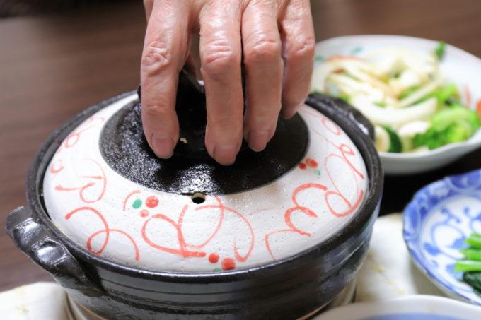 祖母(おばあ)が土鍋のフタを開けようとしているところ