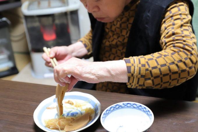 手づかみでタケノコの煮物を食べる祖母