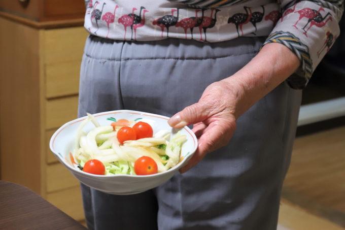 晩ごはんのサラダを持ってきた祖母(おばあ)