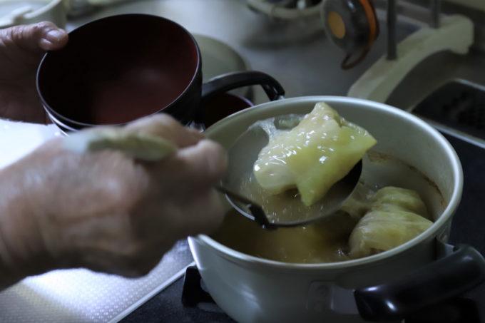 祖母(おばあ)がロールキャベツをお椀によそっているところ