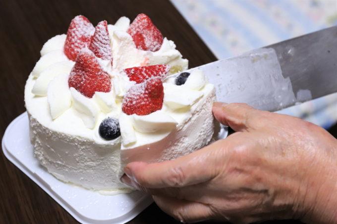 切った誕生日ケーキを包丁で取り分けているところ