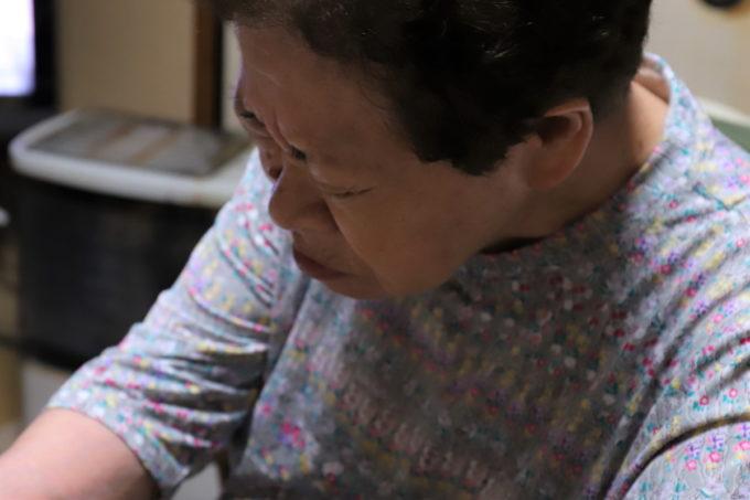 いちごを食べて酸っぱい顔をしている祖母(おばあ)