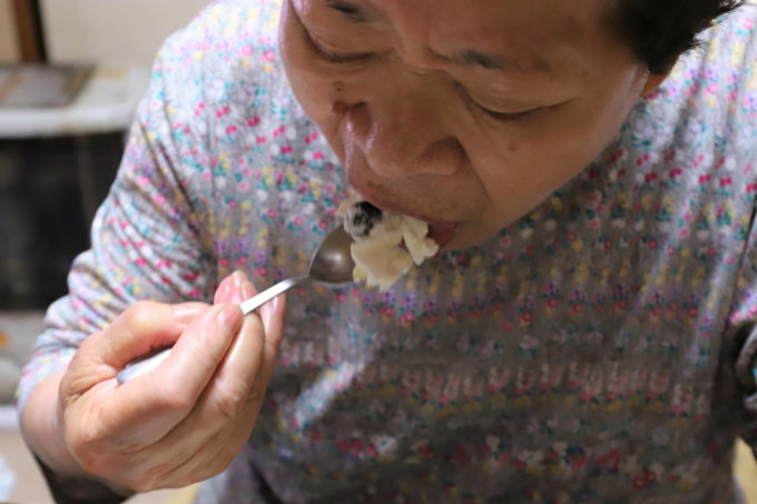 誕生日ケーキをスプーンで食べている祖母(おばあ)