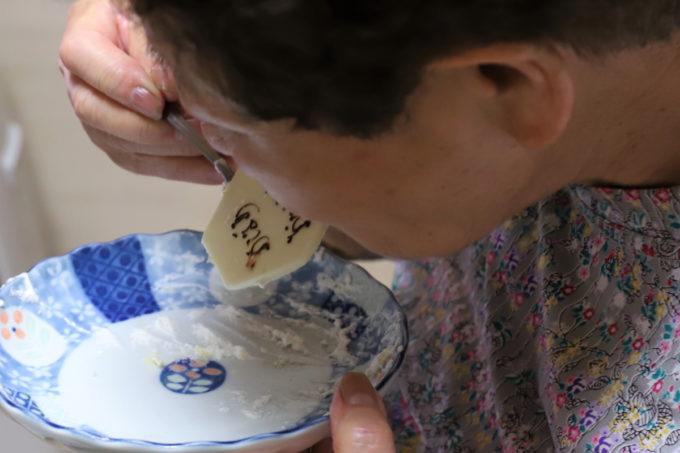 誕生日ケーキのネームプレートを食べている祖母(おばあ)
