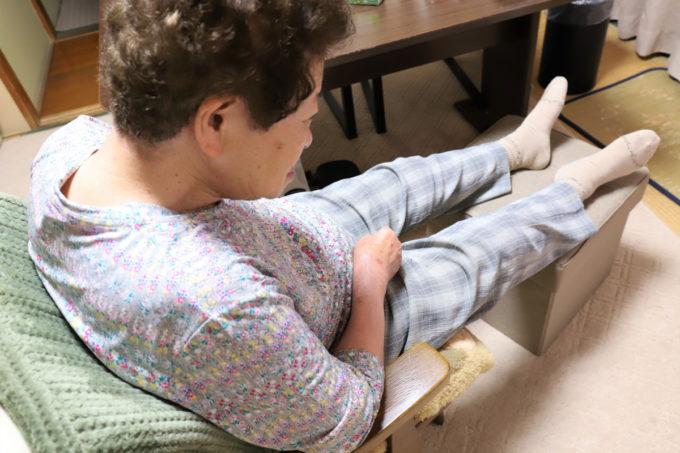 オットマンに足を乗せ、椅子に座ってくつろいでいる祖母(おばあ)