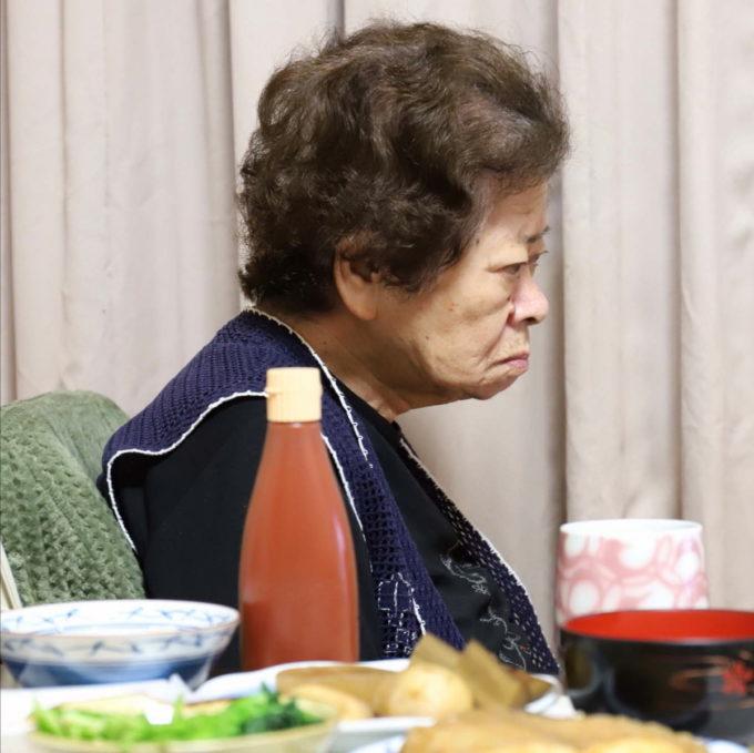 祖母(おばあ)がイスに座り、晩ごはんとケチャップのチューブがテーブルに並んでいる。