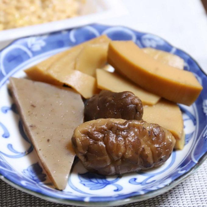 タケノコとコンニャクとシイタケの煮物が皿に盛られている