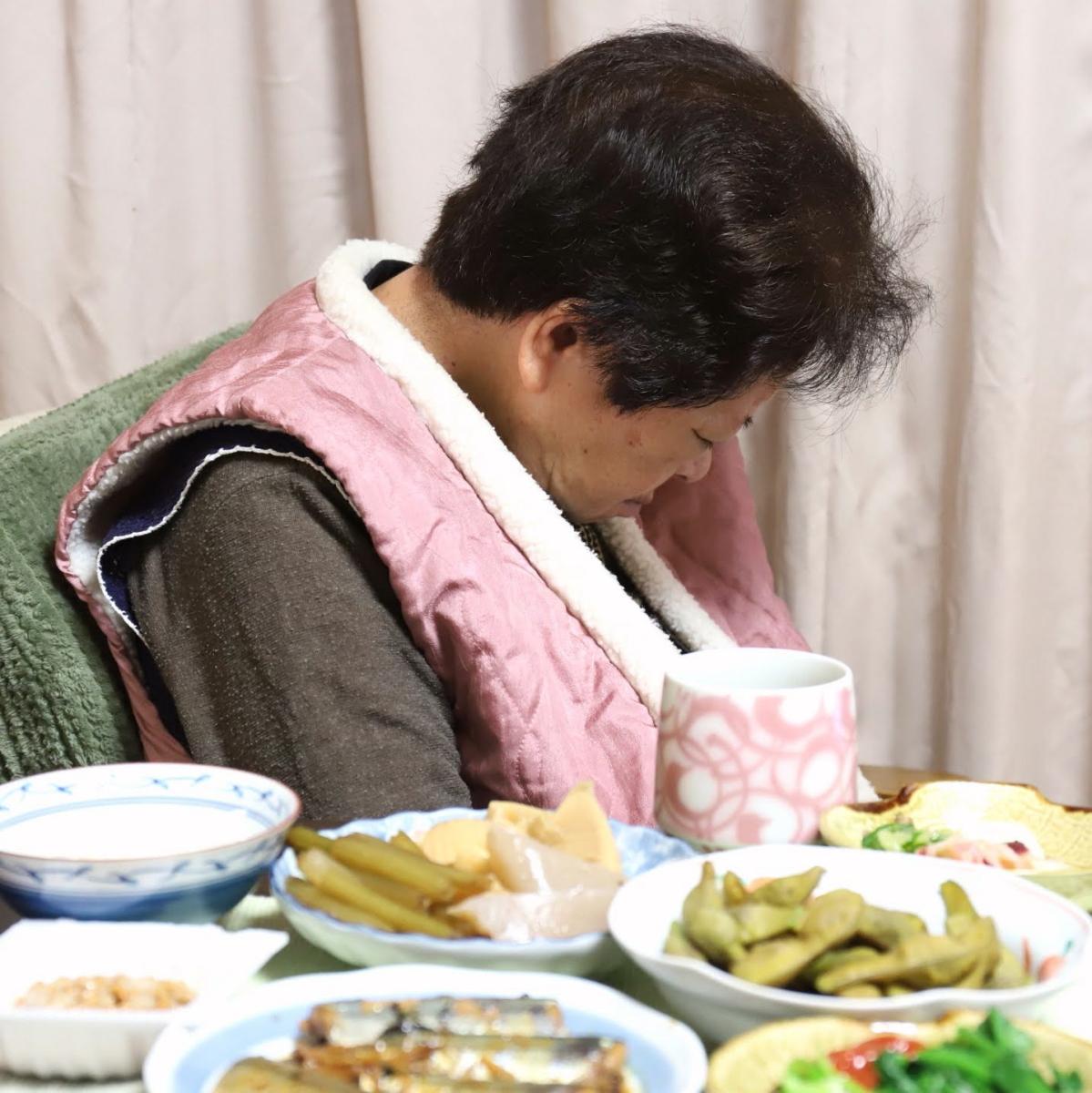 はんてんを羽織って座ったまま寝ている祖母(おばあ)と、手づくりの豪華な晩ごはん