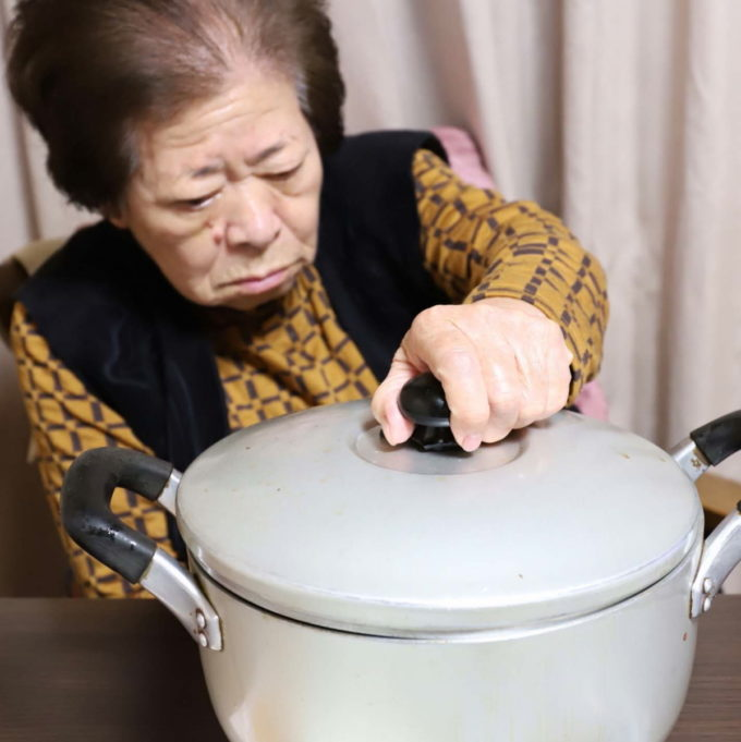 大きな鍋のフタを掴む祖母(おばあ)