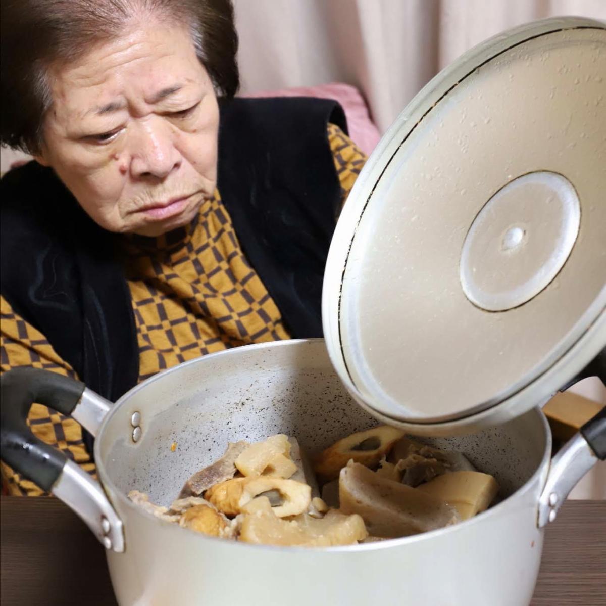 おでんの鍋のフタを持ち上げる祖母(おばあ)