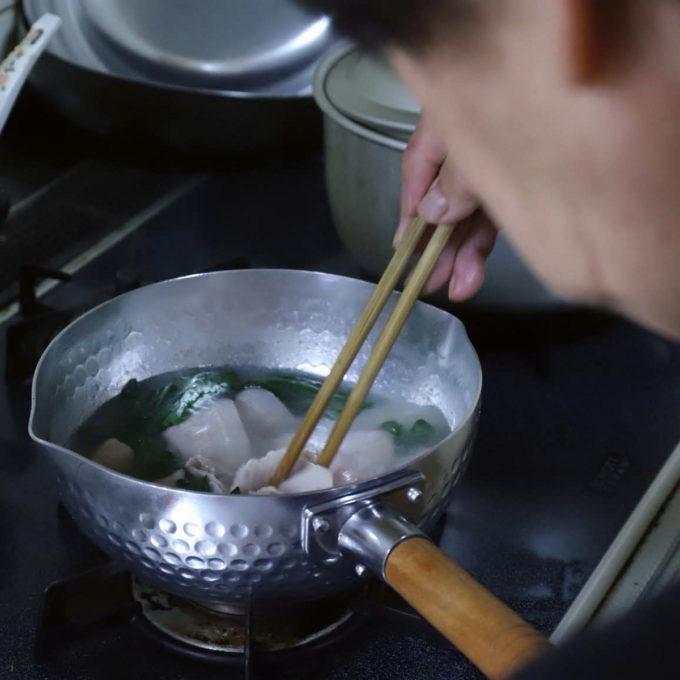 鍋で豚バラ肉とほうれん草を茹でる祖母(おばあ)