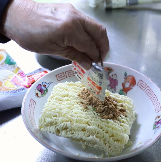 ラーメン丼ぶりにサッポロ一番みそラーメンの麺と粉末スープを入れているところ