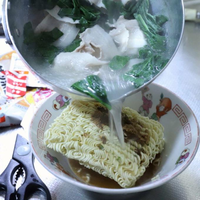 サッポロ一番みそラーメンの麺に具材入りのお湯をかけていることろ