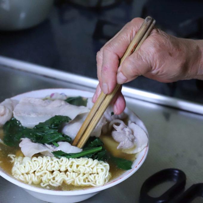 ラーメン丼ぶりに入ったサッポロ一番みそラーメンの麺を菜箸で押さえているところ