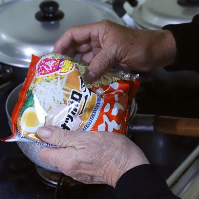 祖母(おばあ)が手に持つサッポロ一番みそラーメンの袋