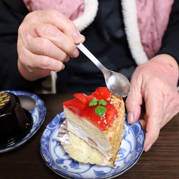 祖母(おばあ)がイチゴのケーキに手を伸ばしている