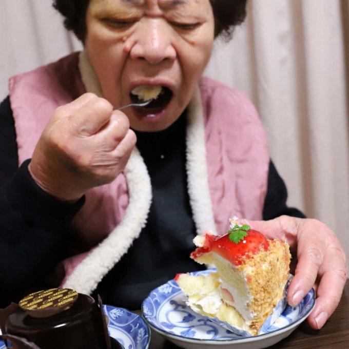 クリスマスのケーキをスプーンですくって食べている祖母