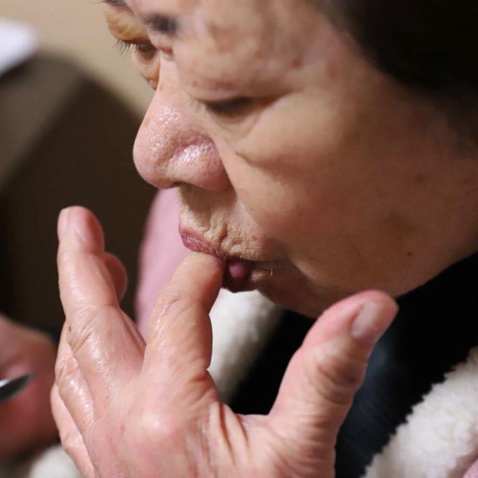 ケーキのクリームがついた指を舐めている祖母
