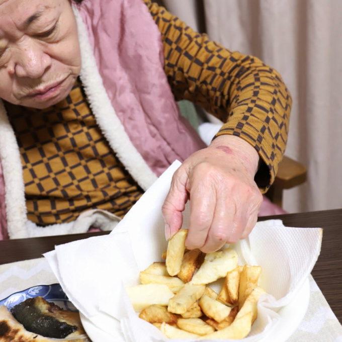 手作りのフライドポテトを摘まむ祖母