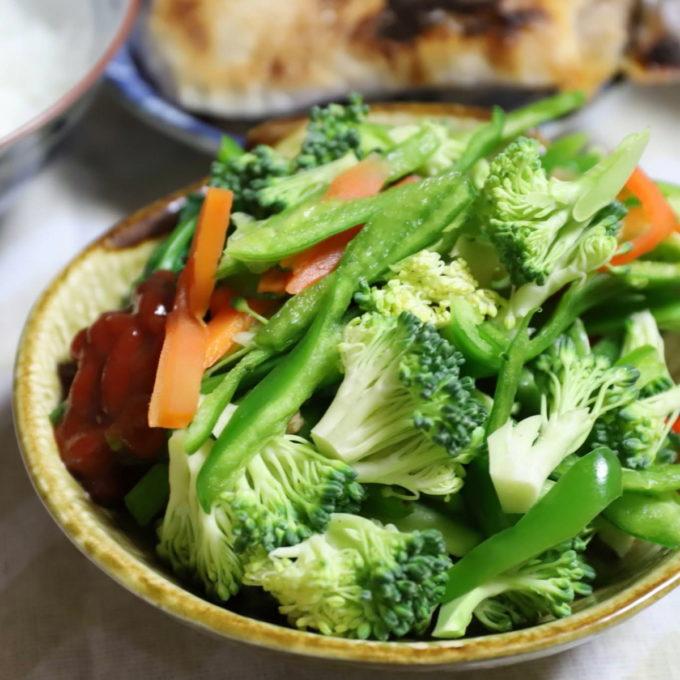 皿に盛られた生ブロッコリーと生ピーマン、茹でほうれん草とニンジンのサラダ