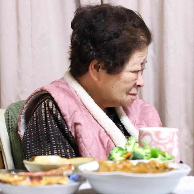 イスに座ってくつろぐ祖母(おばあ)と唐揚げカレーや焼き魚など、晩ごはんのメニュー