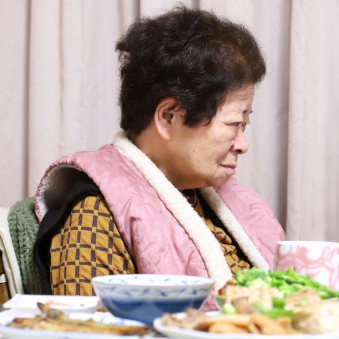 イスに座ってテレビを見ている祖母(おばあ)とテーブルの上の晩ごはん