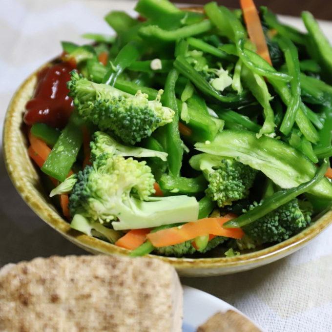 生ピーマン、茹でほうれん草、ブロッコリー、ニンジンを皿に盛りつけたサラダ