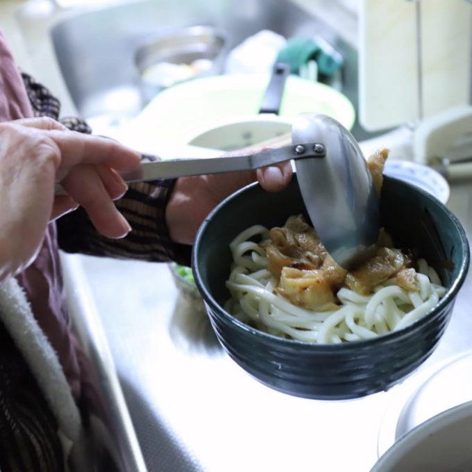 うどんの入った丼ぶりにダシをお玉ですくってかけているところ