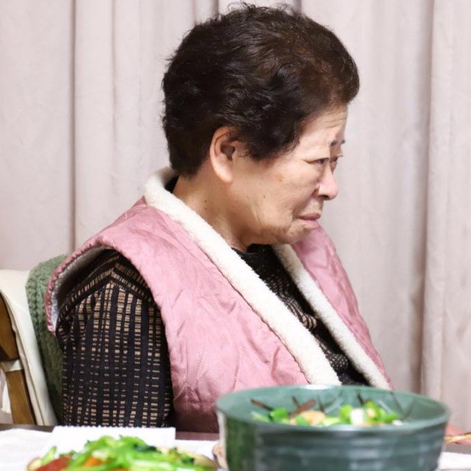 イスに座った祖母(おばあ)とテーブルに並んだ晩ごはん