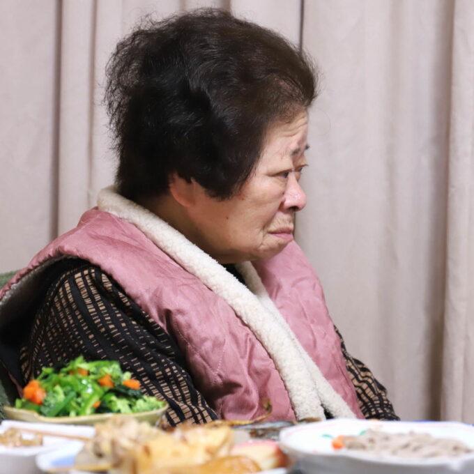 イスに座ってテレビを見ている祖母と、晩ごはんが並んだ食卓。