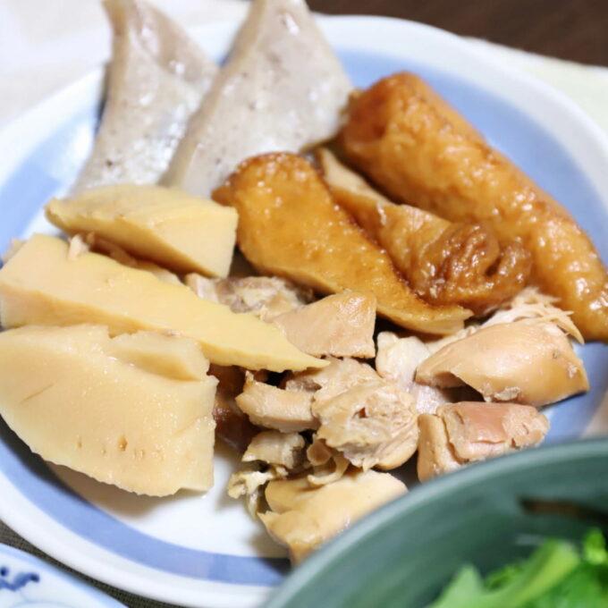 皿に乗った、タケノコと鶏肉とちくわとコンニャクの煮物
