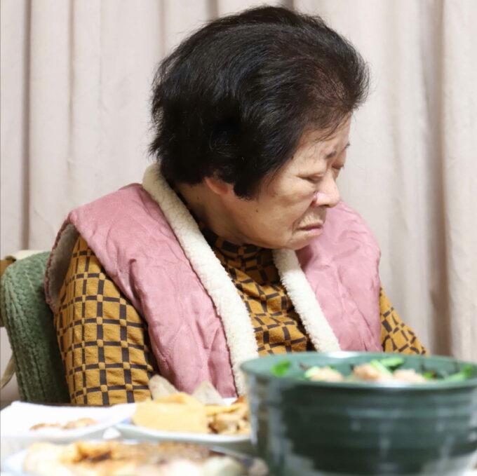 祖母が作った晩ごはんの食卓と、イスに座ったまま寝ている祖母(おばあ)