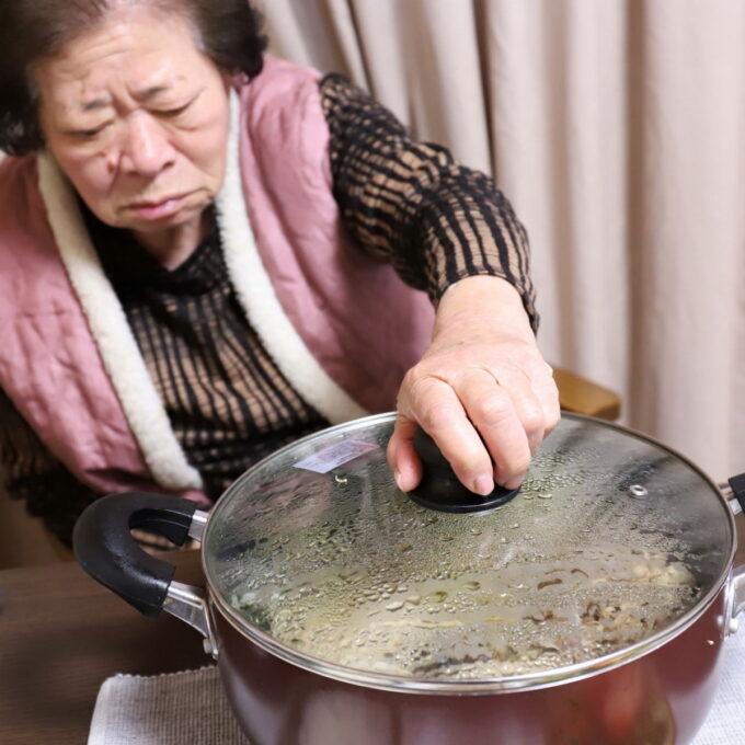 祖母がすき焼きの鍋のフタに手をかけているところ