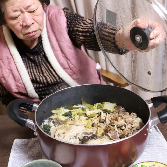 祖母(おばあ)がすき焼きの鍋のフタを持ち上げているところ