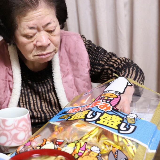 ピーナッツのおつまみの袋に手を入れている祖母(おばあ)