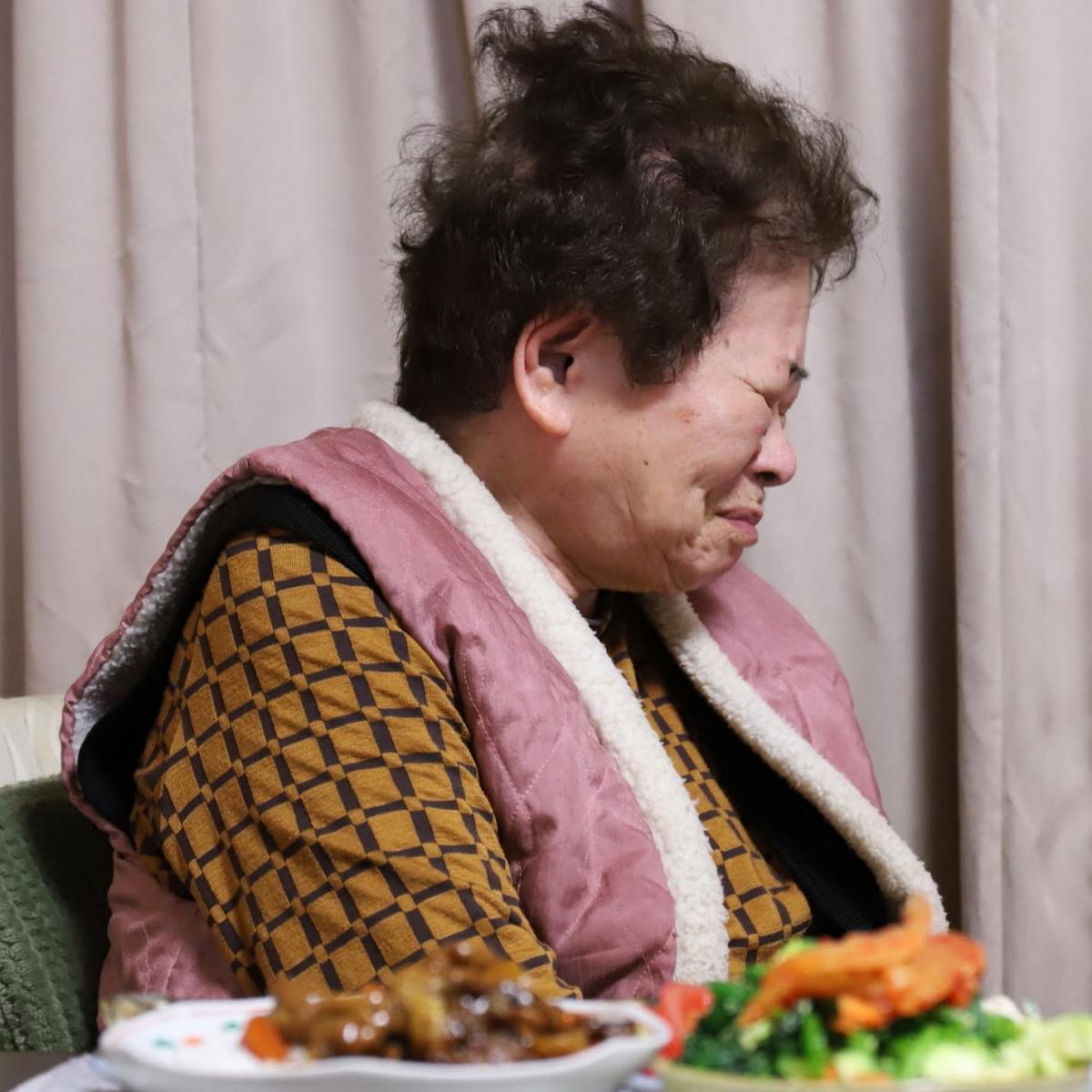晩ごはんの食卓について笑っている祖母(おばあ)