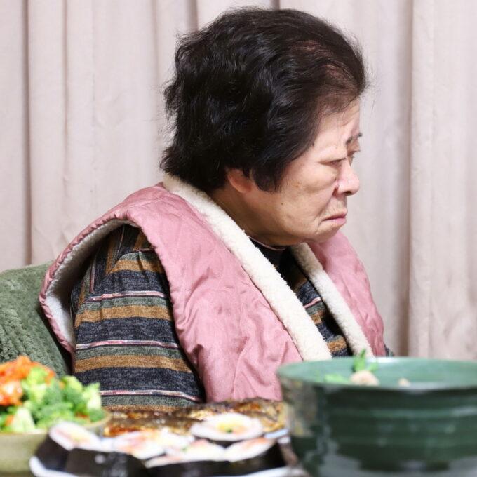 節分の日に晩ごはんをテーブルに並べ、イスに座っている祖母(おばあ)