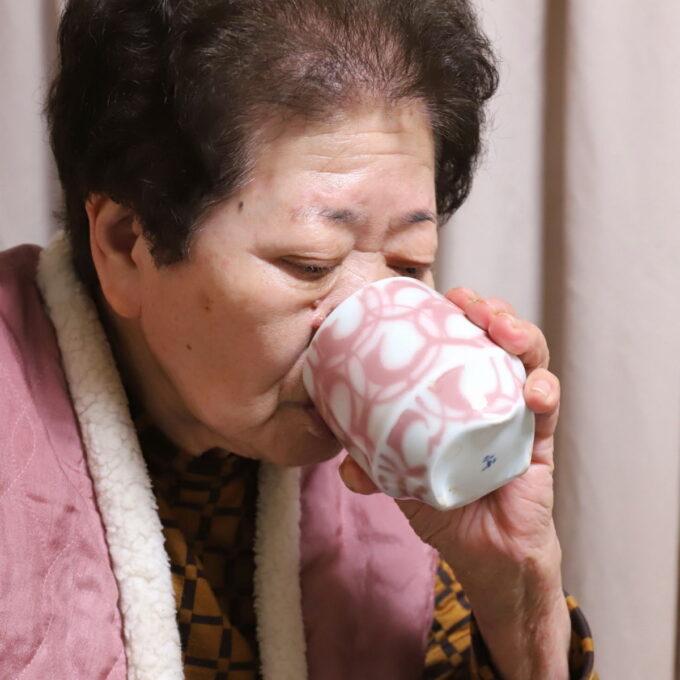ケーキを平らげてお茶を湯呑ですする祖母(おばあ)