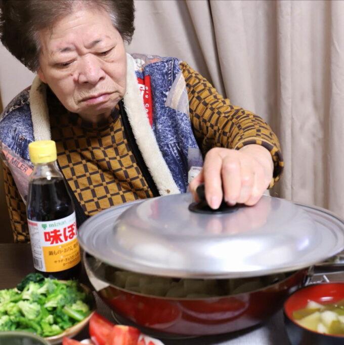 食卓で餃子を焼いたフライパンのフタと持ち上げようとする祖母