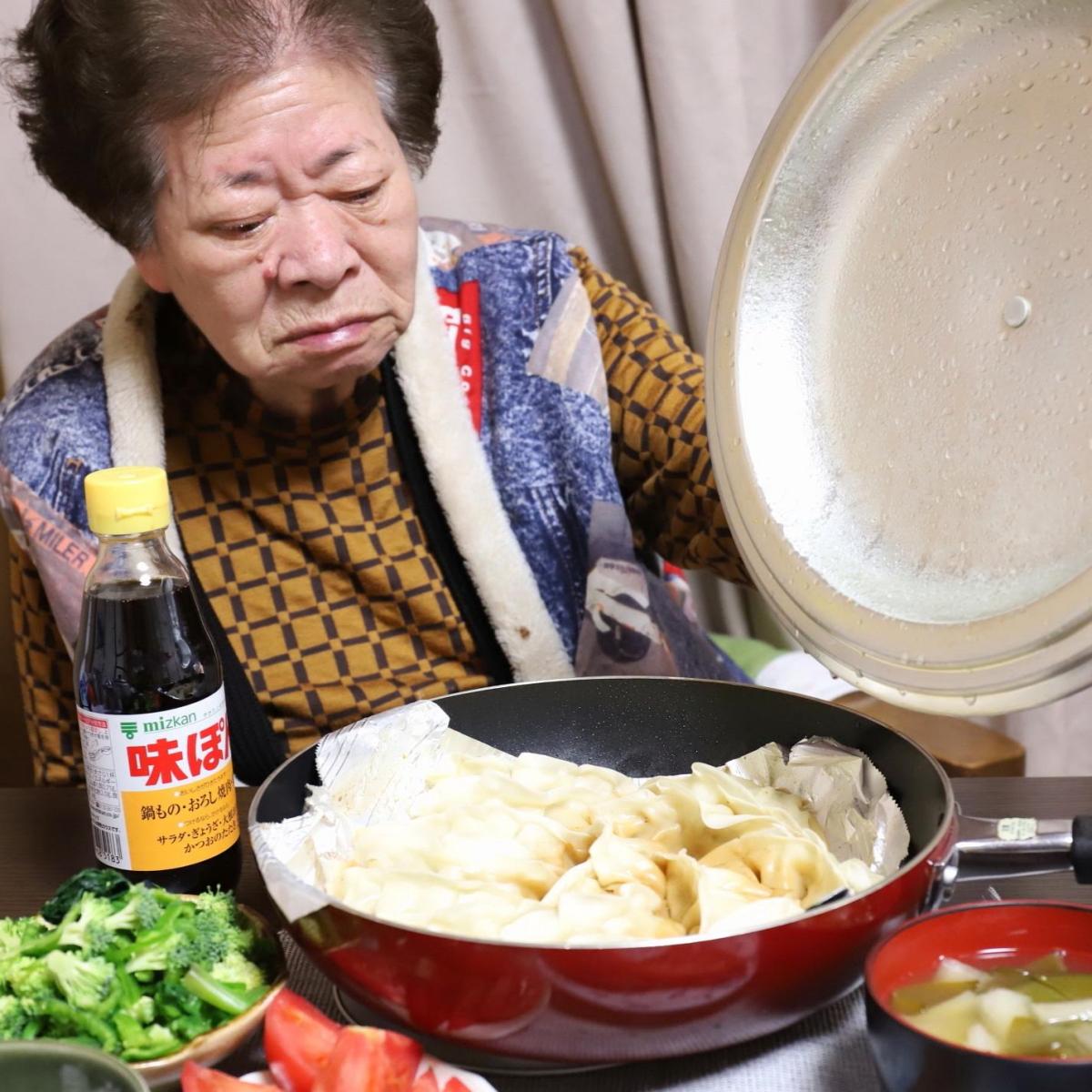 餃子を焼いたフライパンのフタを持ち上げているところ