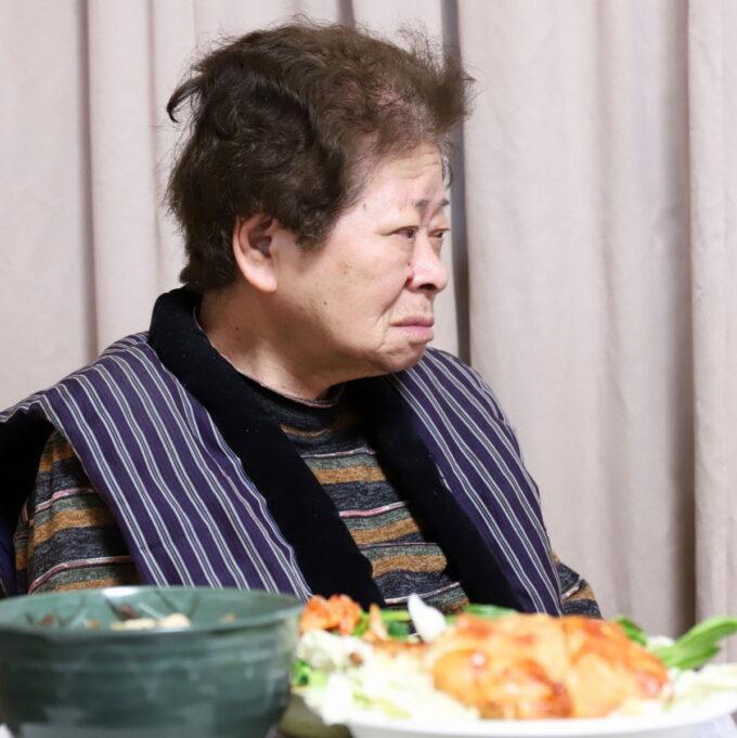 ひな祭りの料理を用意して席に着いている祖母