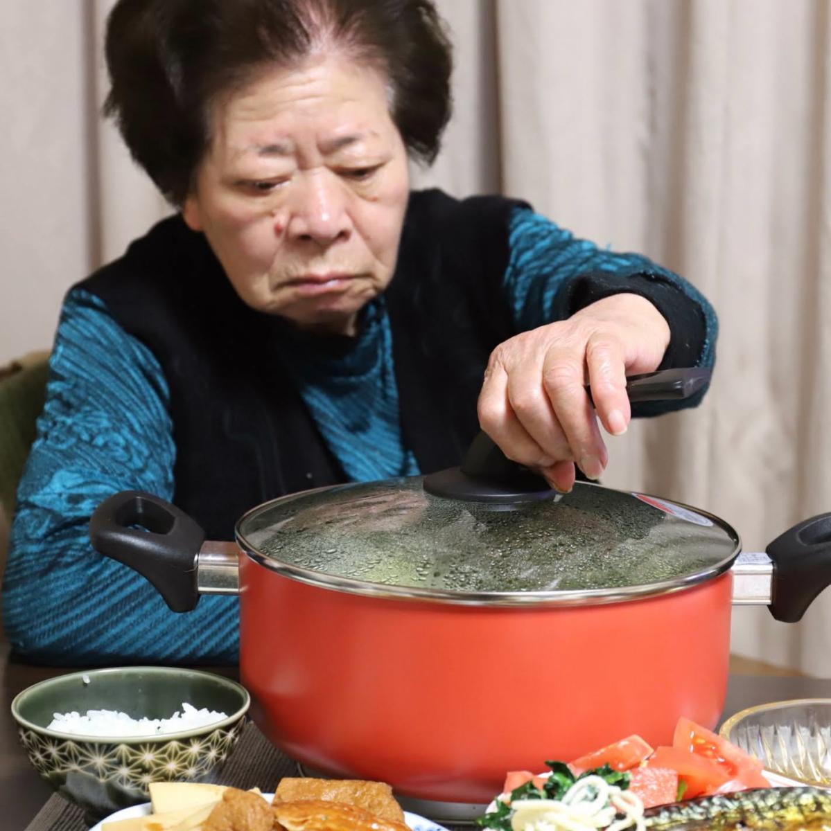 食卓で鍋のフタを取ろうとする祖母(おばあ)