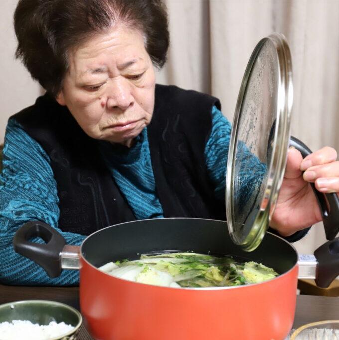 食卓で鍋のフタを持ち上げる祖母(おばあ)