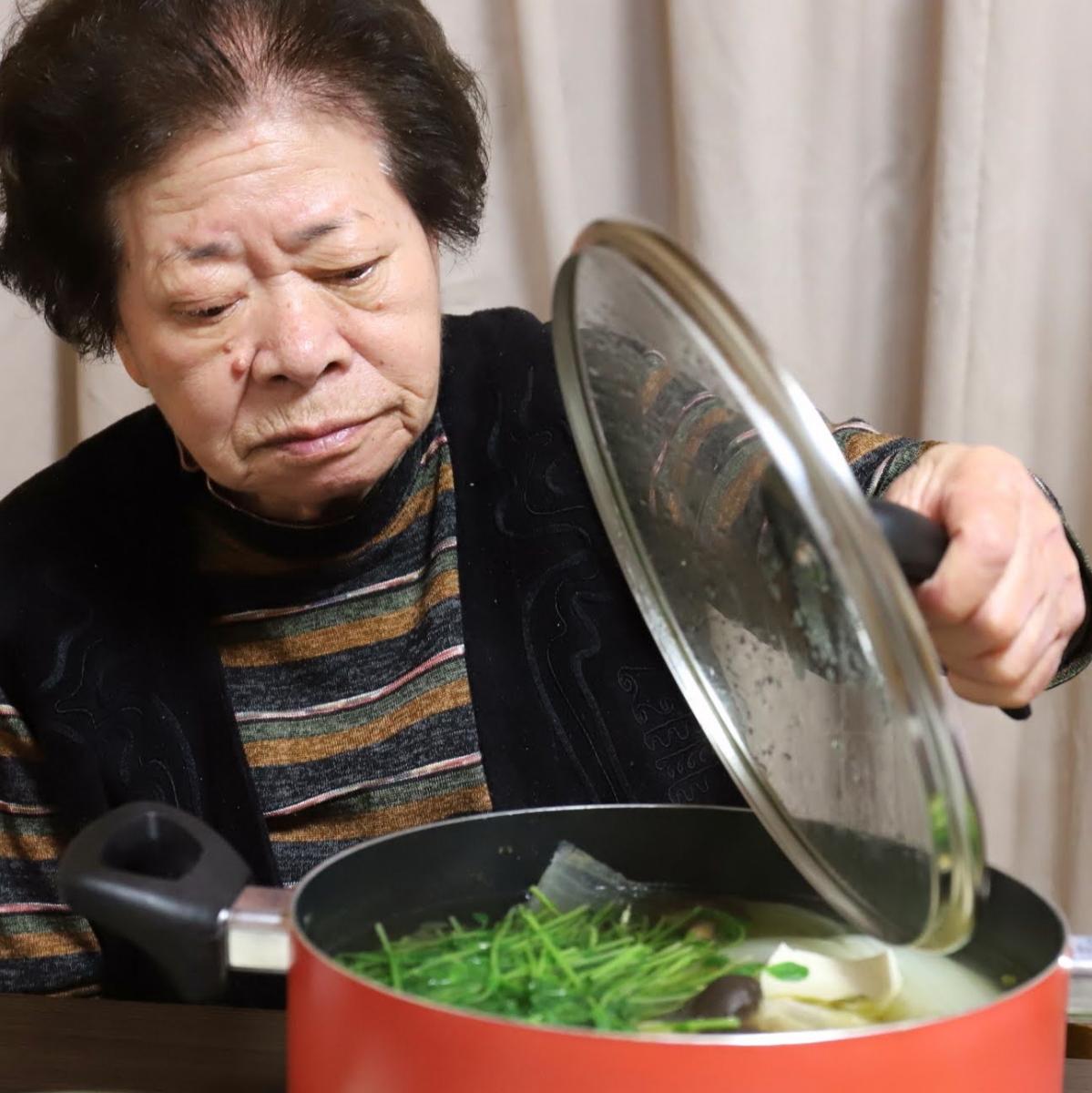 水炊きの鍋のフタを開けている祖母(おばあ)