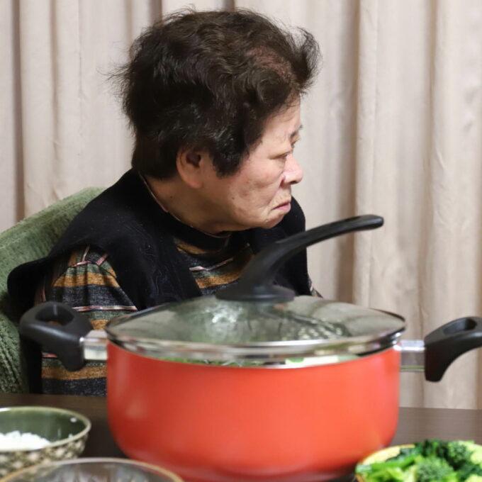 夕飯の水炊きの鍋を前にしてテレビを見ている祖母